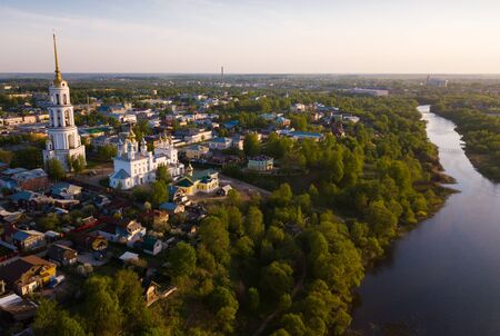Scenic view from drone of Shuya Orthodox Resurrection cathedral with standalone bell tower on background with Teza River and cityscape, Russia