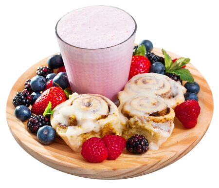 Sweet dessert of homemade cinnabons cinnamon rolls and yogurt smoothie with diversity fresh berries. Isolated over white background