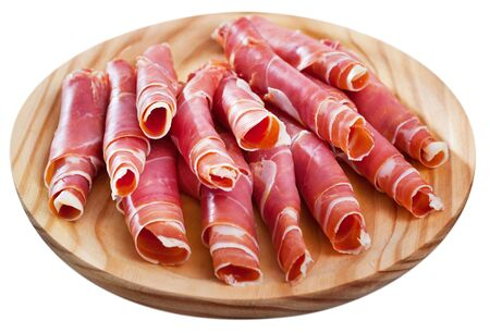 Rolls of thin slices of dry-cured ham served on wooden board. Isolated over white background