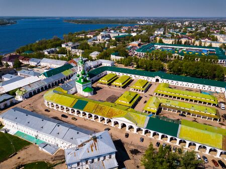 Aerial view of five-domed Saviour church with tall belltower on territory of Gostiny Dvor in Kostroma on background with cityscape and Volga River, Russia Фото со стока