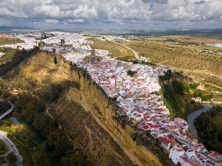 Aerial view of ancient city of Arcos de la Frontera located on edge of cliff on bank of Guadalete river, Andalusia, Spain 写真素材