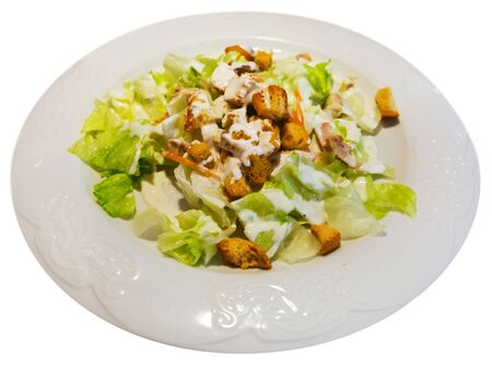 Caesar salad on plate. Isolated over white background