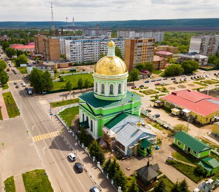 Aerial view of Orthodox Holy Trinity Church on background with cityscape of small Russian town of Ozyory