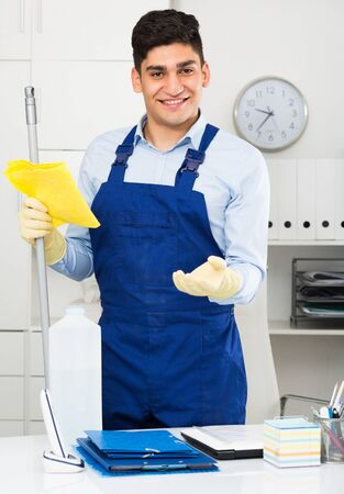 Man cleaner 28-33 years old is ready to clean the cabinet in office. Foto de archivo - 124601469