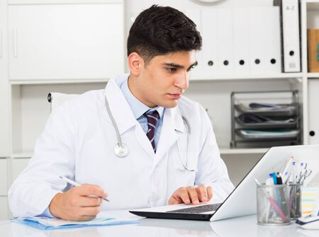 Male doctor 28-35 years old is doing report about patients in hospital.