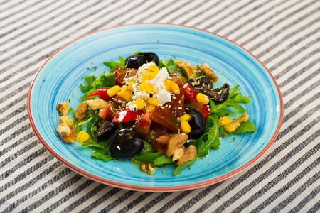 Image of salad with arugula, Feta cheese and walnut on the plate indoors.