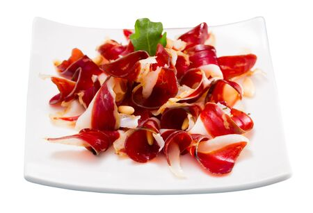 Delicious appetizer dried duck breast magret with pine nuts. Isolated over white background Zdjęcie Seryjne