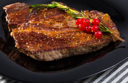 Grilled beef steak served with rosemary on black plate