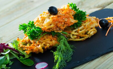 Vegetarian concept. Delicious tempura vegetables with assorted greens, radish and black olives