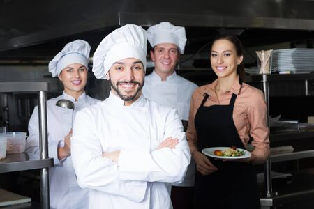 Portrait of confident cheerful adult chef in kitchen with staff of restaurant Stock Photo