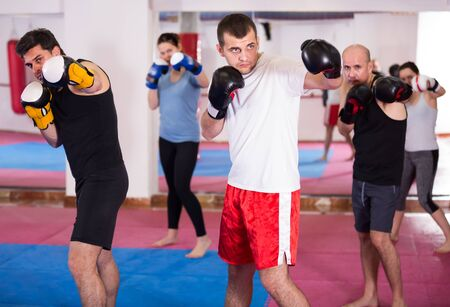 Friendly people practicing boxing punches in the boxing hall