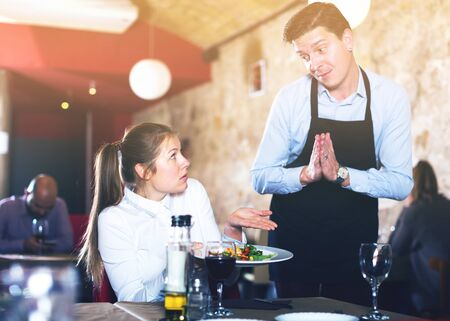 Female client expressing displeasure with food talking to excusing waiter. Focus on woman