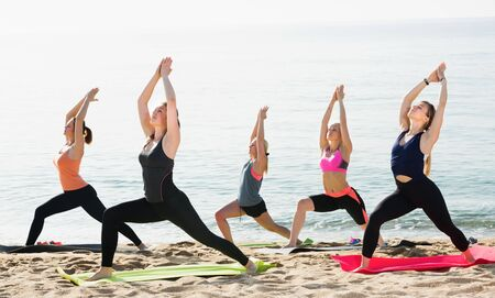 Positive girls exercising yoga positions on sandy beach in sunny morning