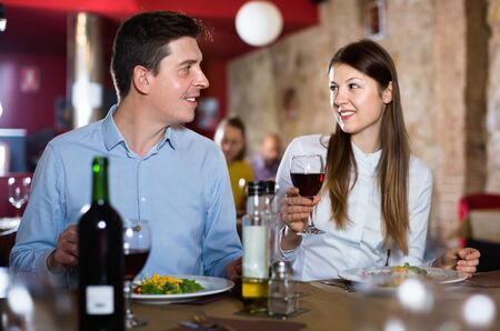 Loving happy cheerful positive smiling pair enjoying evening meal and conversation at cozy restaurant