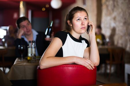 Unhappy female talking on mobile phone sitting apart in restaurant with drunk man behind