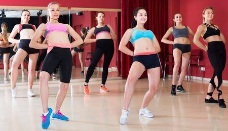 Young smiling women performing dynamic modern dance in fitness studio Standard-Bild