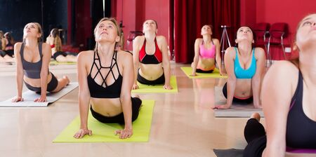 women diligently develop flexibility in training on yoga in the room