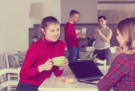 Smiling girl with cup of coffee talking to female traveler who planning itinerary with laptop in kitchen of hostel
