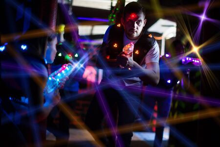 Portrait of guy in colored beams of laser guns during laser tag game on dark arena Фото со стока