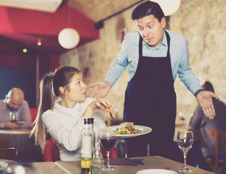 Displeased unhappy young woman conflicting with apologetic waiter because of poor quality of dish in restaurant