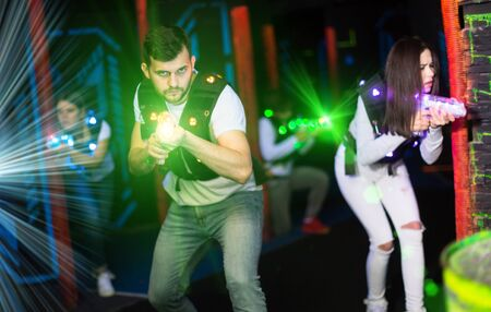 Portrait of guy in colored beams of laser guns during laser tag game on dark arena Banque d'images