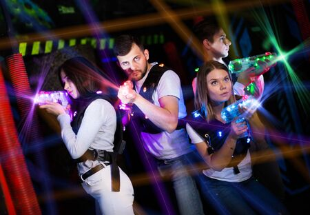 Excited young people in bright beams of laser guns during laser tag game in dark room