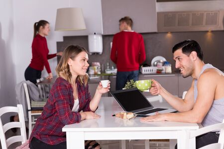 Attractive girl sitting in kitchen of hostel with cup of coffee, talking to guy with laptop
