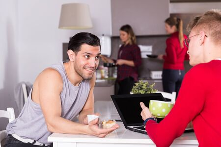 Bearded man friendly discussing with guy who sitting with laptop in common kitchen of hostel Stock Photo