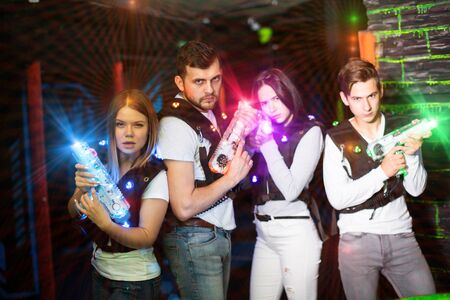 Group portrait of young people in colorful beams of laser guns having fun on lasertag arena Фото со стока