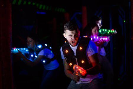 Portrait of young man with laser gun having fun on dark laser tag arena