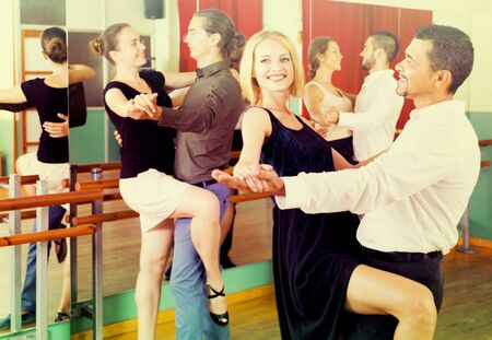 Group of smiling young adults having tango class at dance studio. Selective focus