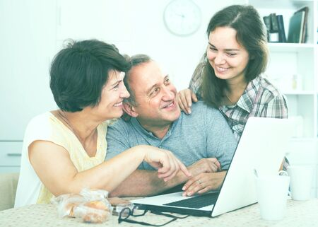 cheerful smiling young woman helping her elderly parents to learn how to use laptop at home 版權商用圖片