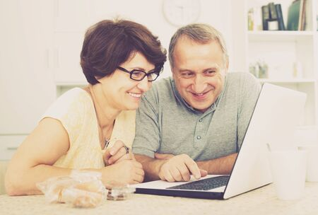 cheerful smiling senior couple looking on laptop screen  indoors at home together 版權商用圖片