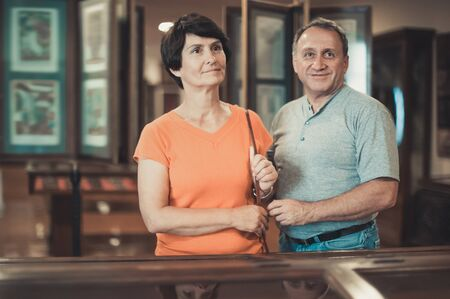 Cheerful mature man and woman visiting museum of applied arts