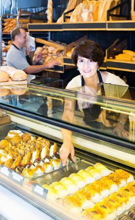 Happy european staff offering fresh baguettes and buns in bakery