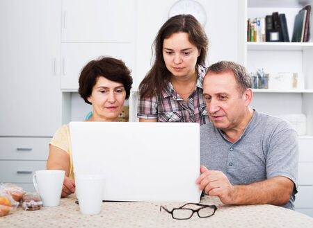 Positive retiree man and woman looking at laptop together with their adult daughter indoors
