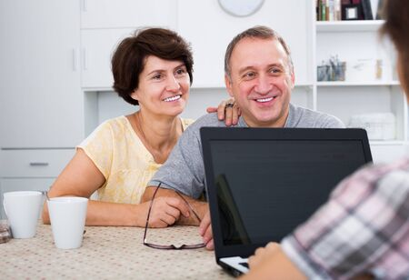 Happy senior couple listening to young woman and looking at her laptop indoors 版權商用圖片