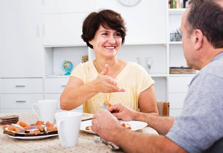 Glad mature woman eating lunch and listening to her husband at home