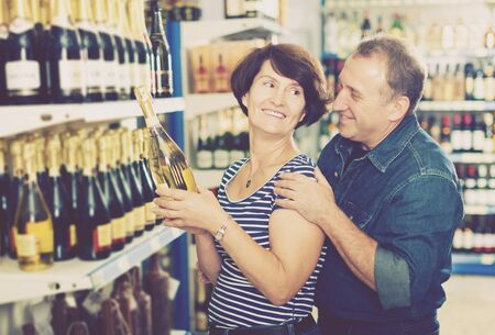 Smiling mature husband and wife selecting a vine at the grocery store