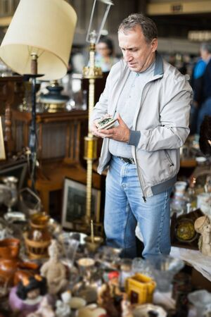 Portrait of senior male choosing vintage goods at flea market