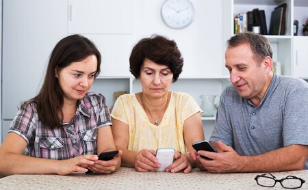 Cheerful senior couple and young woman using mobile phones while sitting together at home. Focus on young woman Banco de Imagens