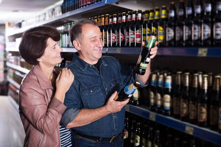 Positive elderly couple among the different kinds of beer at the grocery store