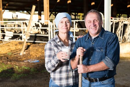 Portrait of couple who are standing near cows at the farm.