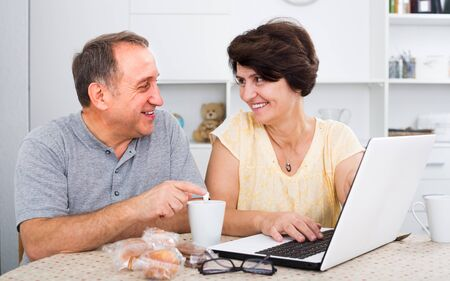 Smiling mature couple looking documents on laptop indoors at home together