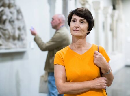 Portrait of positive female visitor who is looking at the exposition in historical museum. Stock Photo