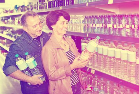 Happy couple with a bottle of water at the grocery store