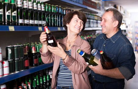 Portrait of  an elderly positive american couple buying a beer at the grocery store Banco de Imagens