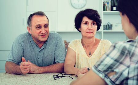elderly parents attentively listening and talking to adult daughter at the table at home Stok Fotoğraf