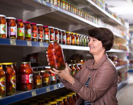 Portrait of an elderly woman buying canned tomatoes at the grocery store