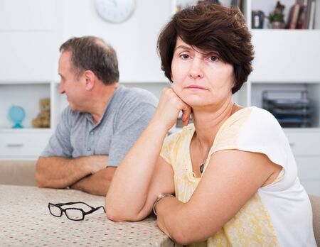 Portrait of worried mature woman having problems with her husband at home
